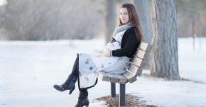 kobieta w ciąży siedząca na ławce, w zimowej scenerii